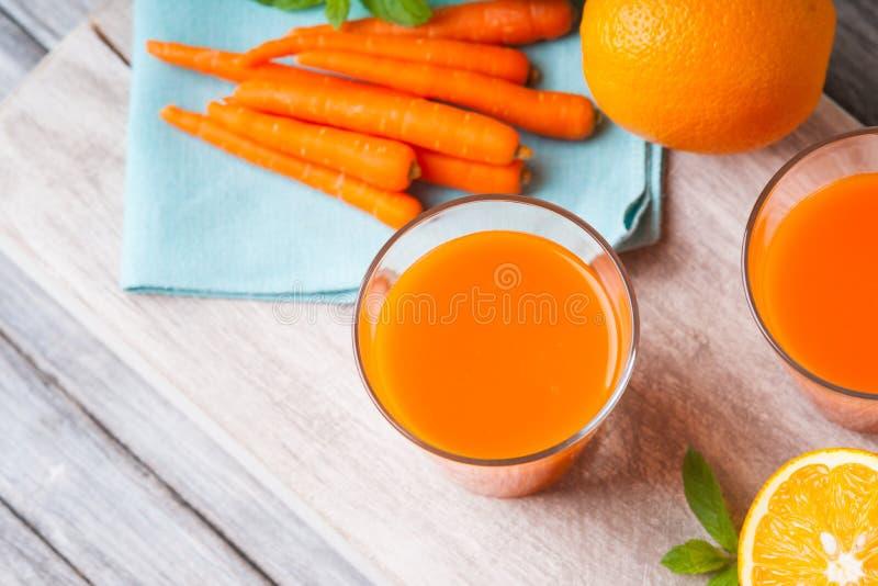 Glazen met wortelsap, wortel, gesneden sinaasappel en muntblad stock foto's