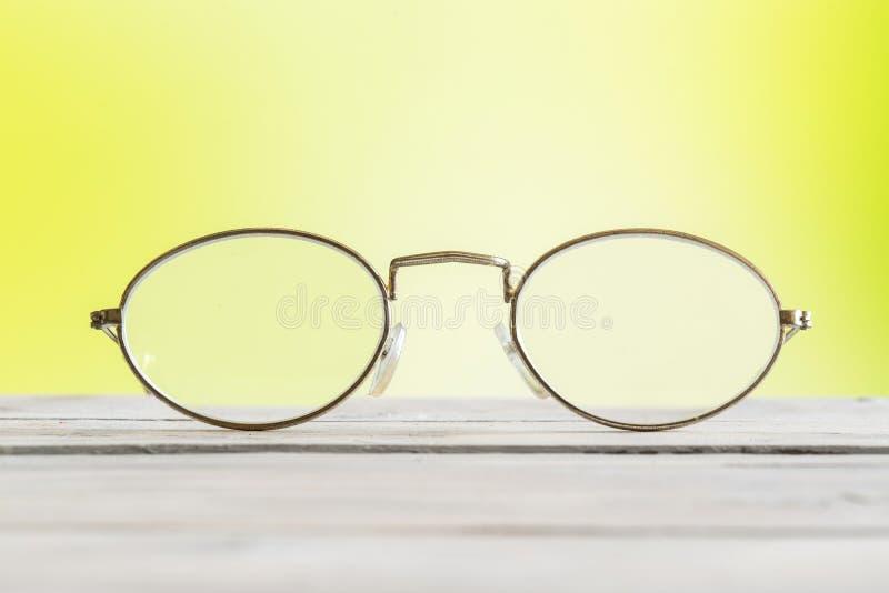 Glazen op een lijst aangaande groene achtergrond stock afbeelding