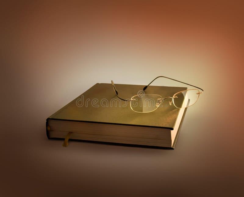 Glazen op het boek stock afbeelding