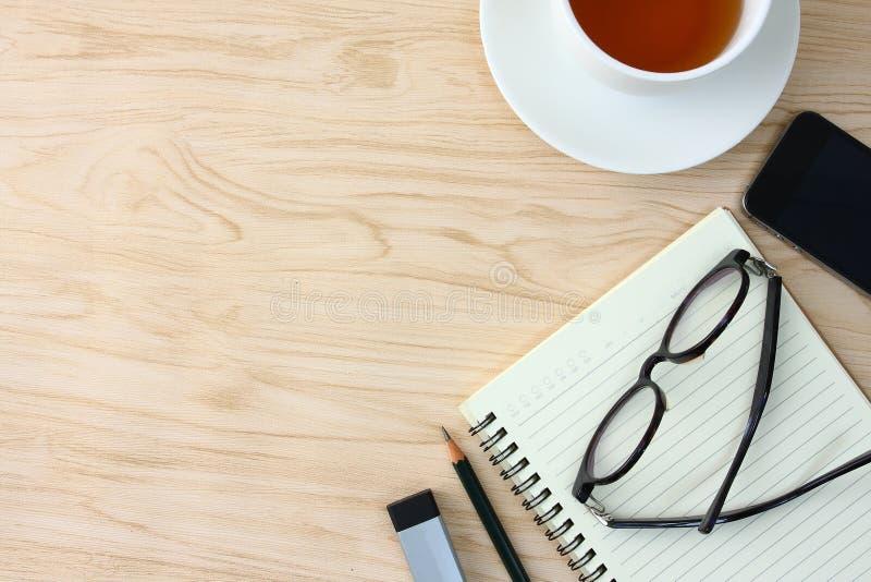 Glazen op het notitieboekje worden geplaatst dat Er zijn telefoons en koffiemokken en ruimte voor het schrijven van tekst stock foto