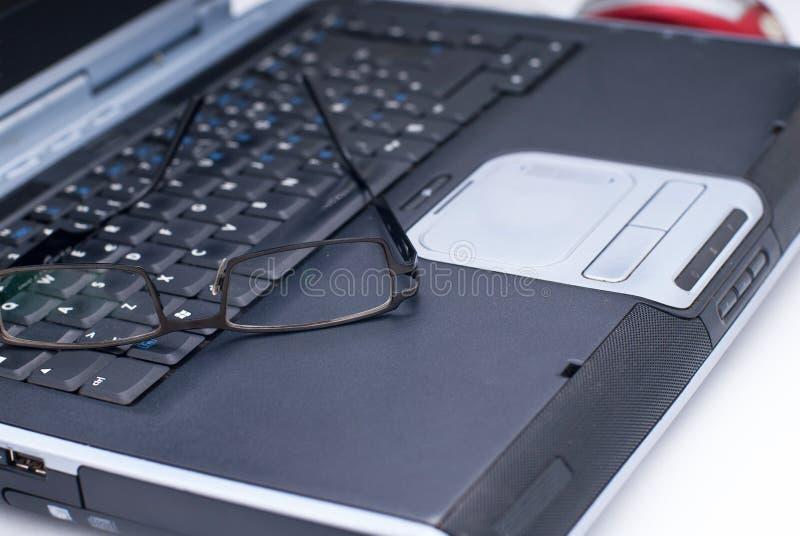 Glazen op laptop stock afbeeldingen