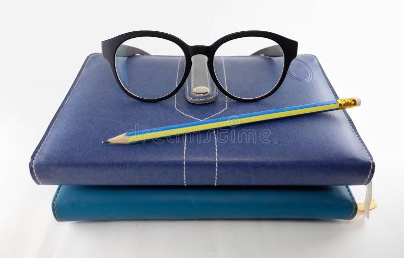 Glazen, potlood en stapel van boeken royalty-vrije stock foto