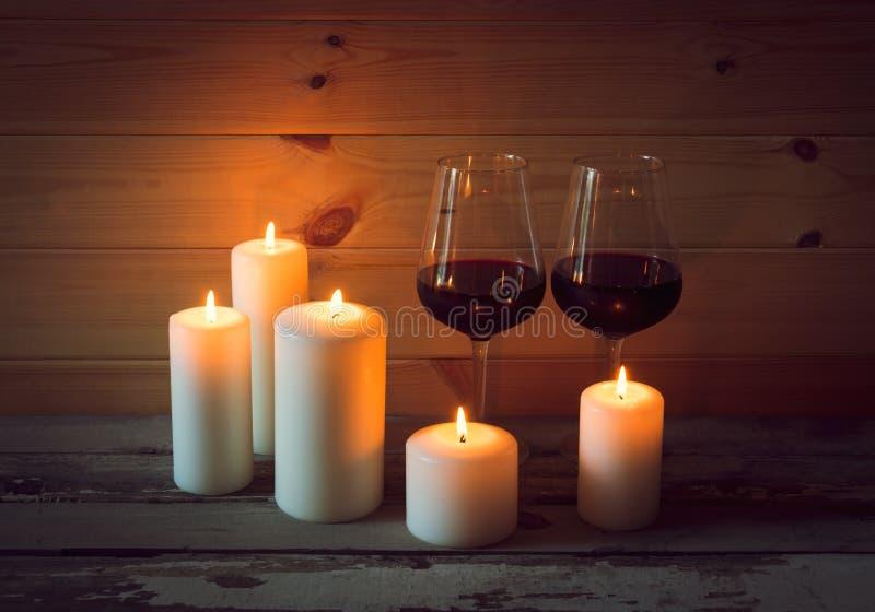 Glazen rode wijn met kaarsen op houten achtergrond stock fotografie