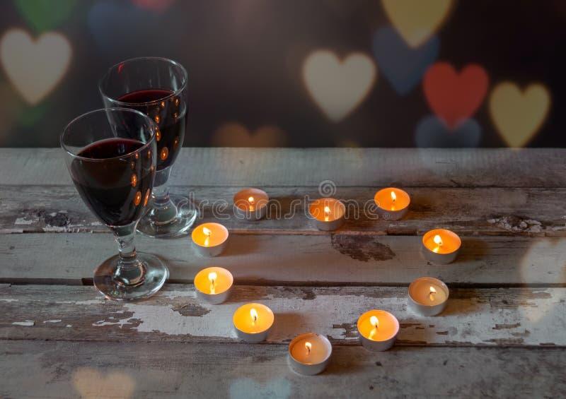 Glazen rode wijn met kaarsen op oude houten lijst stock foto