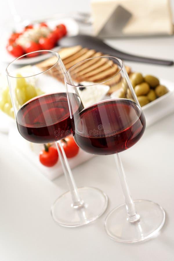 Glazen rode wijn met voorgerecht stock foto's