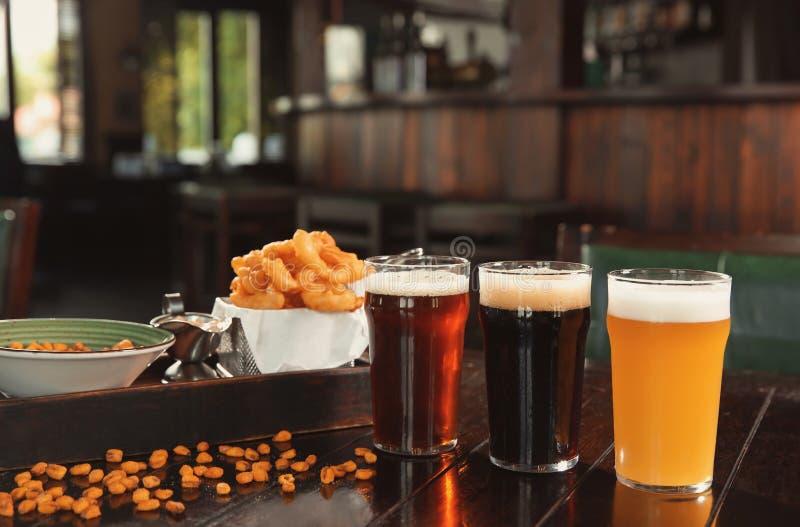 Glazen smakelijke bier en snacks op houten lijst royalty-vrije stock fotografie