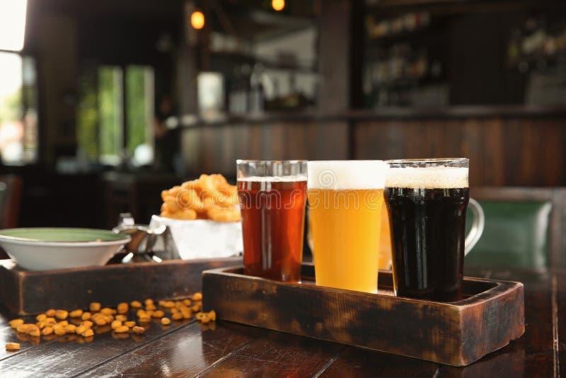 Glazen smakelijke bier en snacks op houten lijst stock fotografie