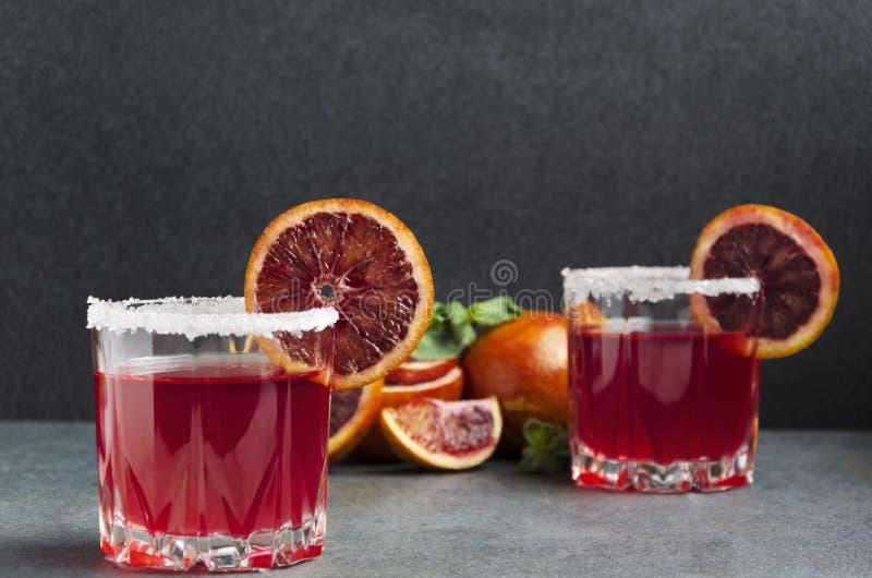Glazen van bloedsinaasappel margarite met gezouten rand, munt en plakken van vruchten stock afbeeldingen