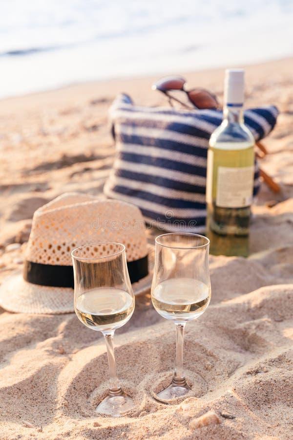 Glazen van de witte wijn op het zonsondergangstrand, picknickthema stock foto