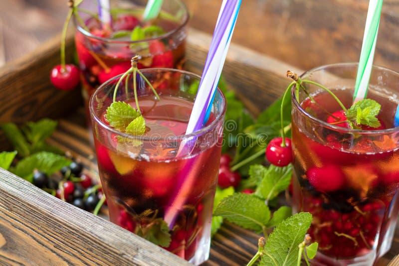 Glazen van het verfrissen van drank met vers fruit en decor op smaak dat worden gebracht dat royalty-vrije stock afbeeldingen