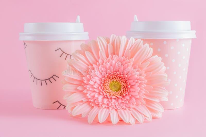 Glazen van koffie meeneem en gerberabloem op roze pastelkleurachtergrond De tijd van de koffie Met exemplaarruimte royalty-vrije stock fotografie