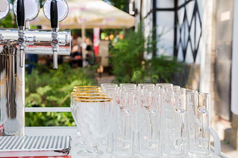 Glazen voor bier en een biertapkraan op het de zomerterras stock fotografie