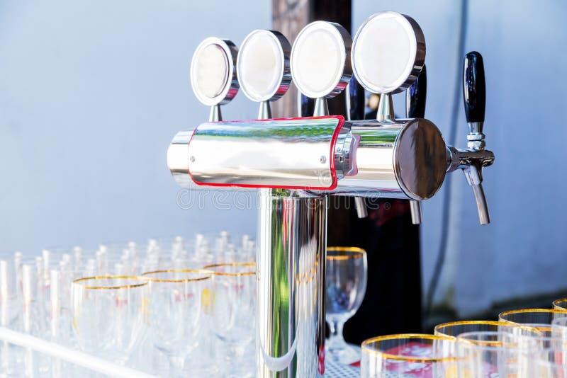 Glazen voor bier en een biertapkraan op het de zomerterras stock afbeelding