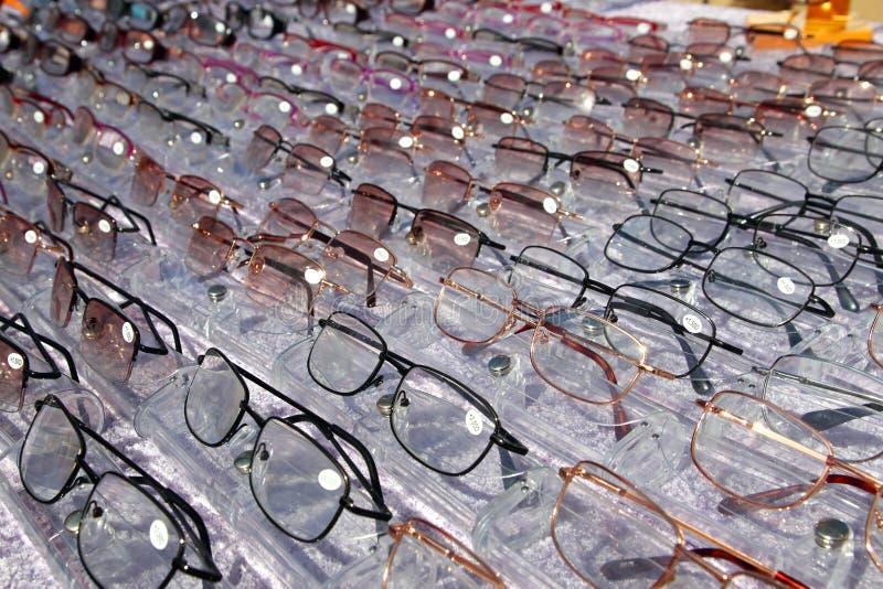 Glazen voor dichte omhooggaande mening in rijen vele oogglazen stock afbeeldingen