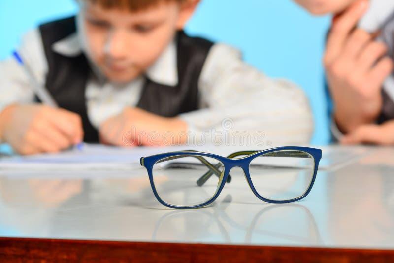 Glazen voor gezicht tegen de achtergrond van kinderen die lessen in school maken royalty-vrije stock afbeelding
