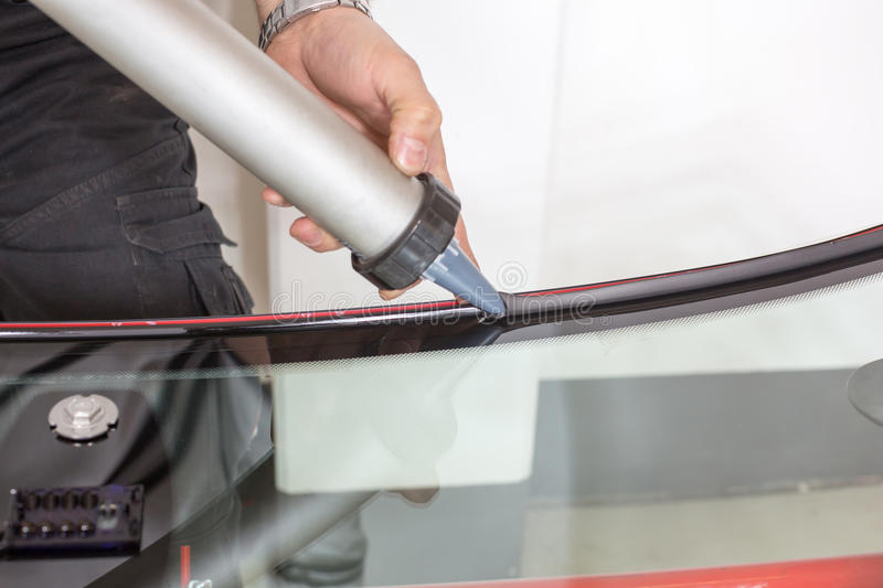 Glazier applying rubber sealing to windscreen. Glazier applying rubber sealing to windshield in garage stock photography