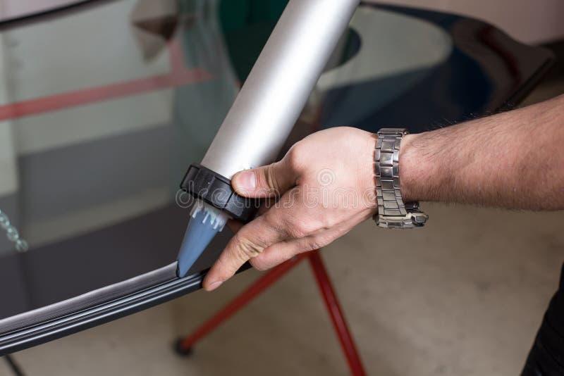 Glazier applying rubber sealing to windscreen. Glazier applying rubber sealing to windshield in garage stock image