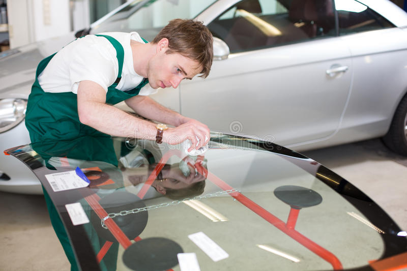 Glazier with car windshield made of glass. Glazier handling car windshield or windscreen made of glass in garage stock photography