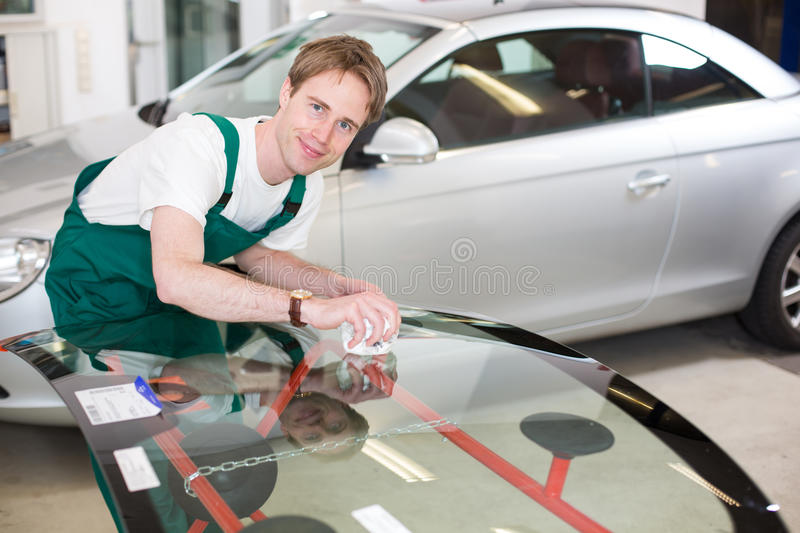 Glazier with car windshield made of glass. Glazier handling car windshield or windscreen made of glass in garage stock photos