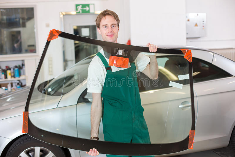 Glazier with car windshield made of glass. Glazier handling car windshield or windscreen made of glass in garage stock image
