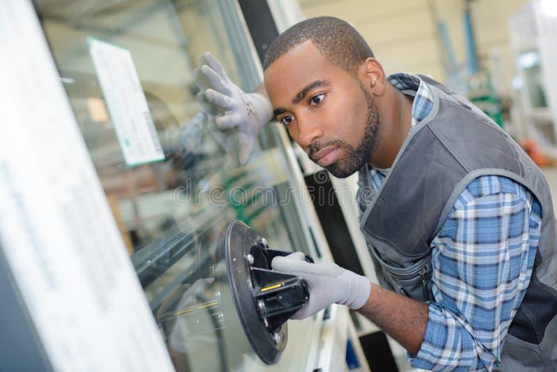 Glazier fixing glass window. Glazier fixing a glass window stock images