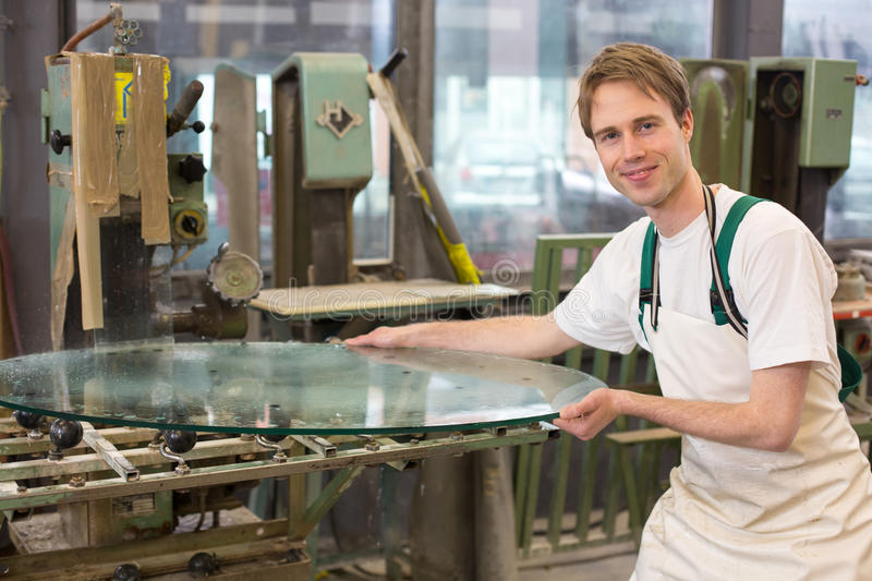 Glazier grinding a pieco of glass. Glazier deburrs a glass on grinding machine in workshop royalty free stock photos
