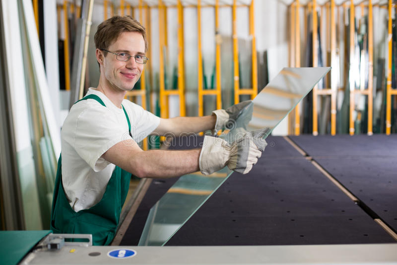 Glazier handling piece of glass in workshop stock photo