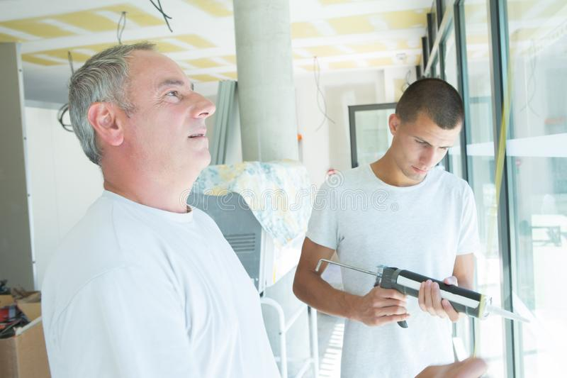 Glazier manager inspecting glass. Glazier manager inspecting the glass stock images