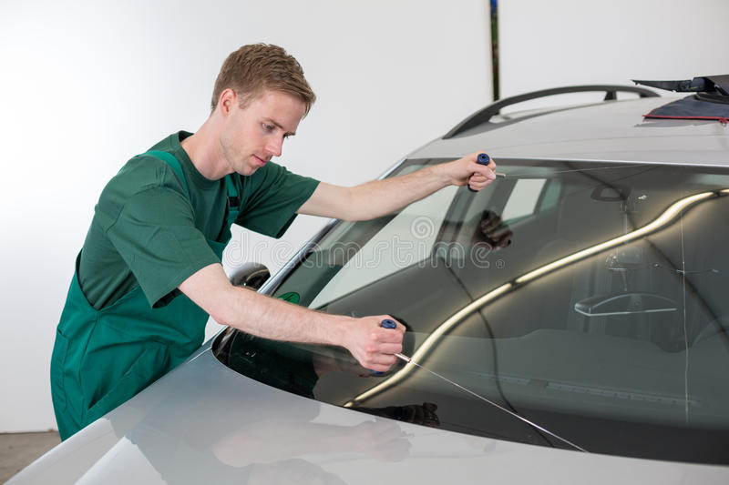 Glazier removing windshield. Glazier cutting adhesive of windscreen with a wire to replace windshield royalty free stock photo