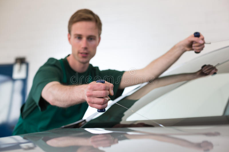 Glazier removing windshield. Glazier cutting adhesive of windscreen with a wire to replace windshield stock photography