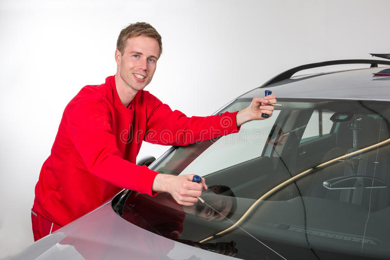 Glazier removing windshield. Glazier cutting adhesive of windscreen with a wire to replace windshield royalty free stock image