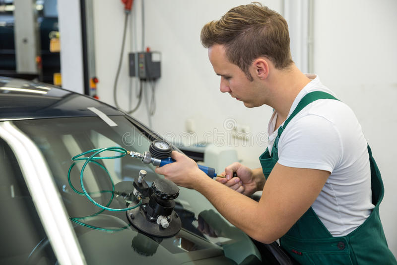 Glazier repairing stone-chipping damage on car's windshield. Or windscreen royalty free stock photo