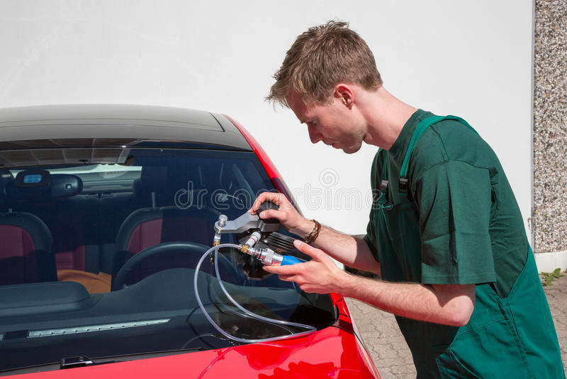 Glazier repairing windscreen after stone chipping damage. Glazier repairing windshield on a car after stone-chipping damage stock images