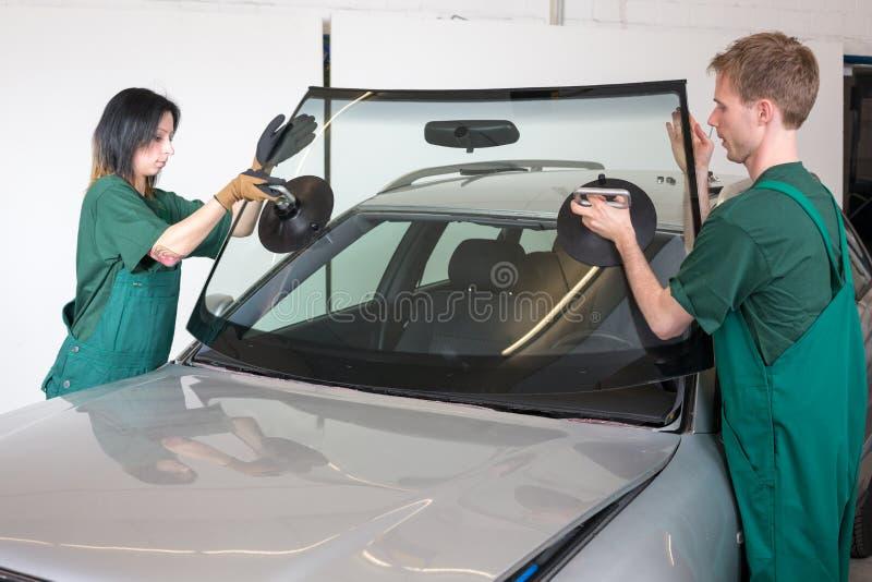 Glazier replacing windshield. Glazier removing windshield or windscreen on a car stock photo