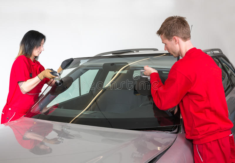 Glazier replacing windshield. Glazier removing windshield or windscreen on a car stock photography