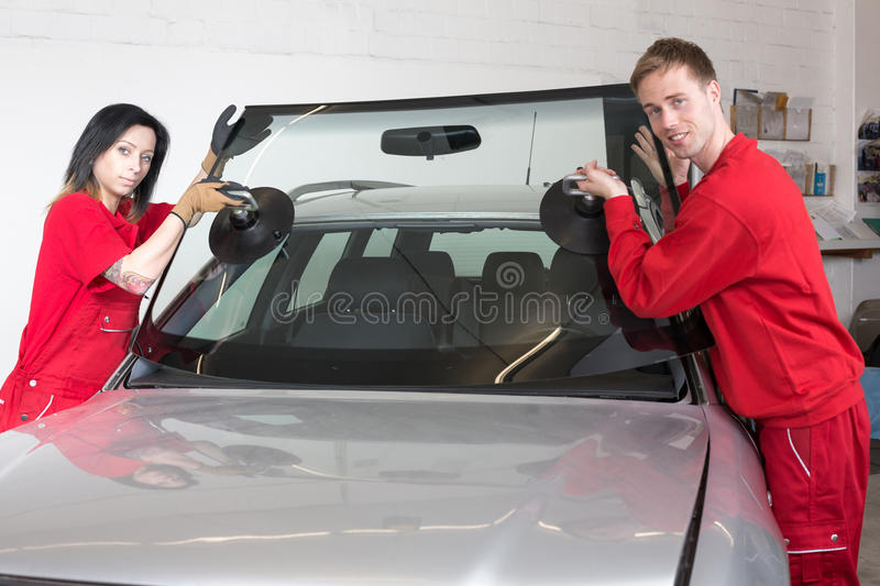 Glazier replacing windshield. Glazier removing windshield or windscreen on a car royalty free stock image