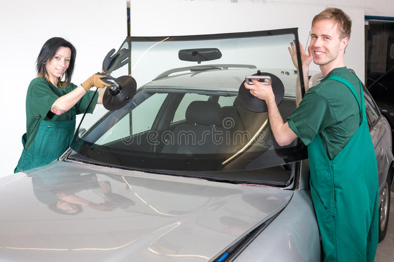 Glazier replacing windshield. Glazier removing windshield or windscreen on a car stock photos