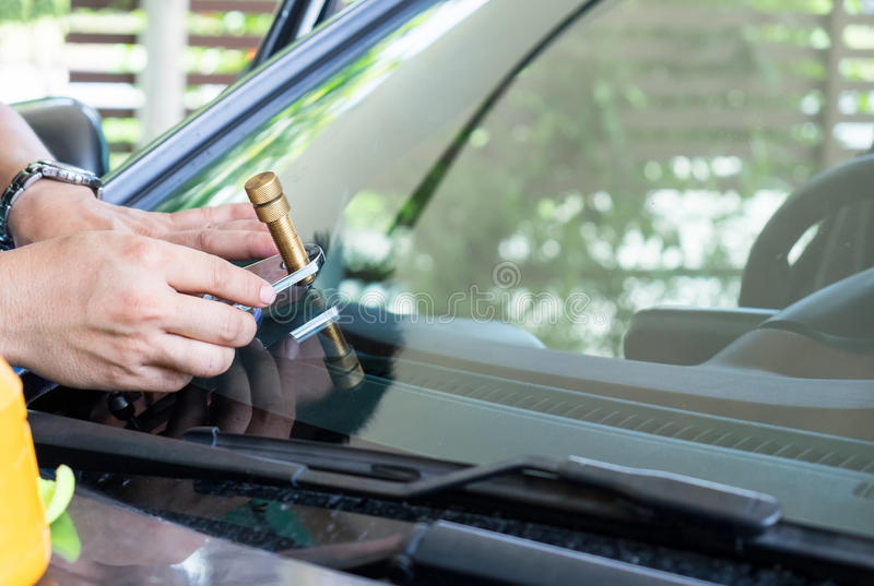 Glazier using tools repair to fix crack windshield. Glazier using tools repairing to fix crack windshield royalty free stock image