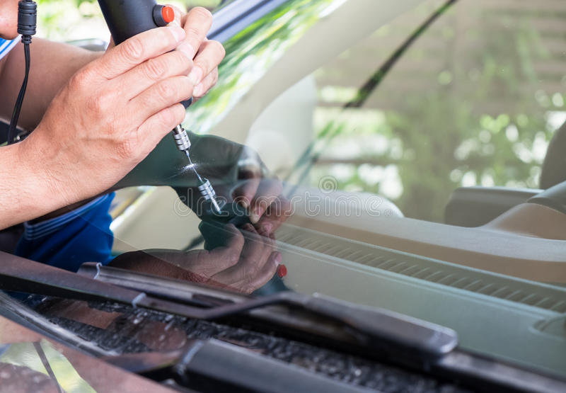 Glazier using tools repairing to fix crack. Windshield stock photos