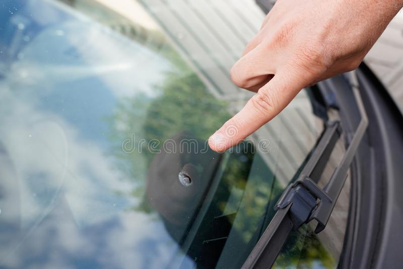 Glazier windscreen on Broken car windshield glass from stone pointed watch of finger hand. A Glazier windscreen on Broken car windshield glass from stone pointed stock photos