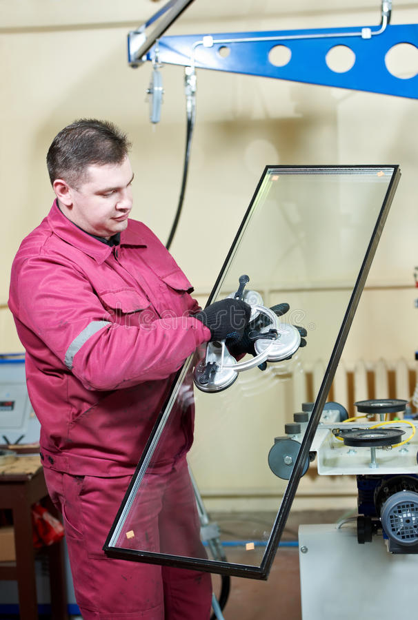 Glazier worker with glass. Glazier worker with suction cup holding glass at double glazing window manufacture royalty free stock images