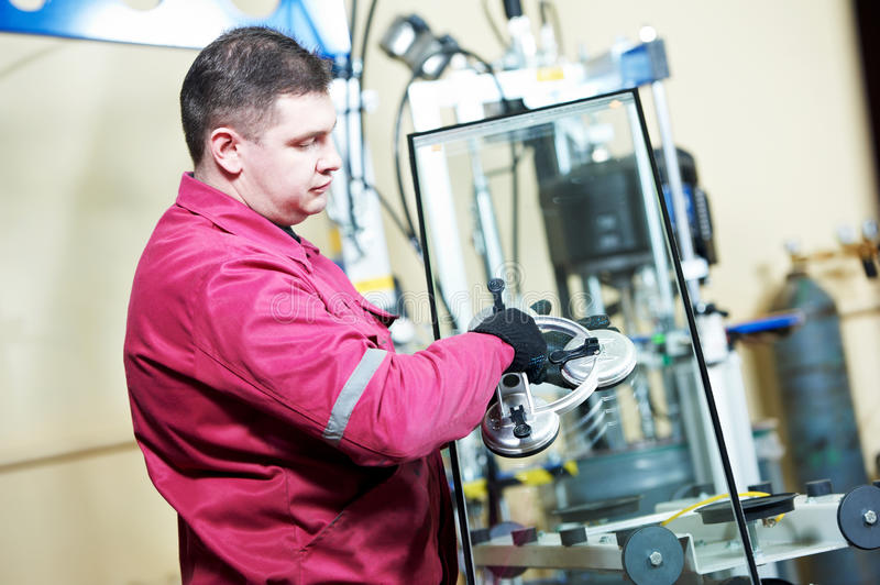 Glazier worker with glass. Glazier worker with suction cup holding glass at double glazing window manufacture stock photos