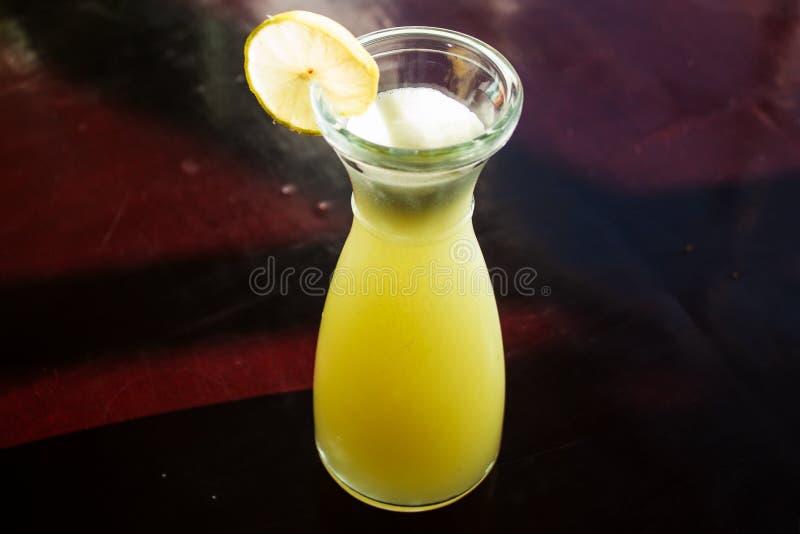 Glazig glas vers gedrukt citroensap met citroen op een donkere lijst Verse sap hoogste mening stock foto