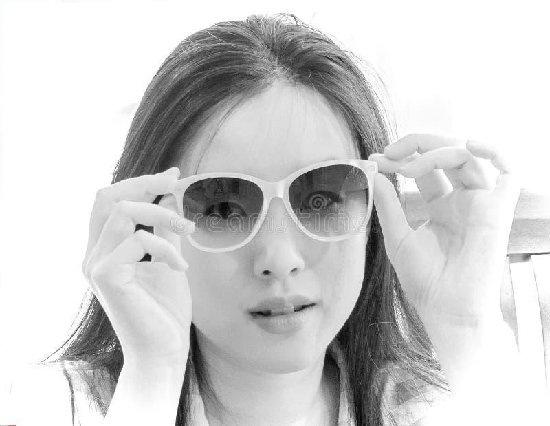 Gleiche der jungen Frau durch Sonnenbrille im einfarbigen hohen Schlüsselbild lizenzfreies stockfoto