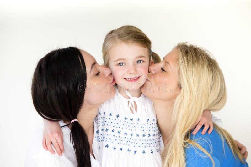Gleichgeschlechtliche Mütter, die ihre Tochter küssen lizenzfreie stockfotos
