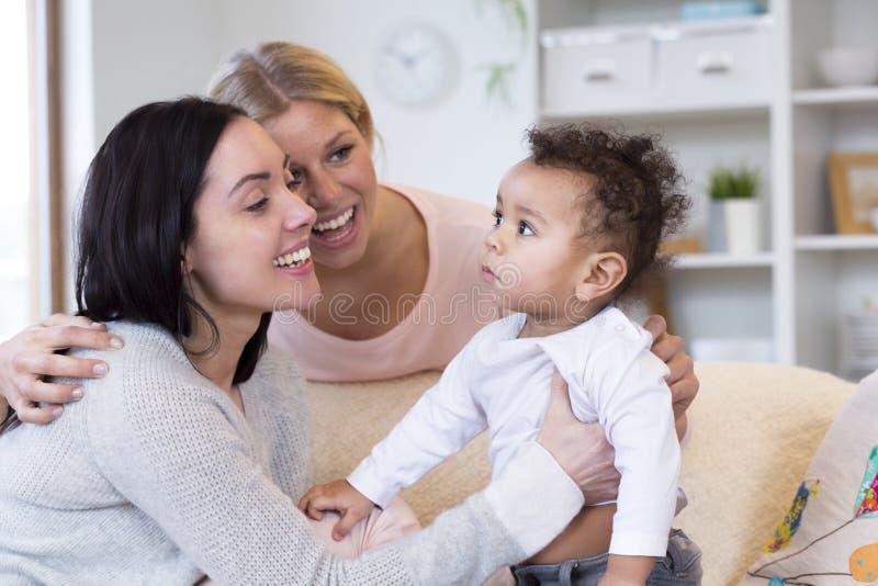 Gleichgeschlechtliche Paare, die ein Getue über Baby machen stockbild