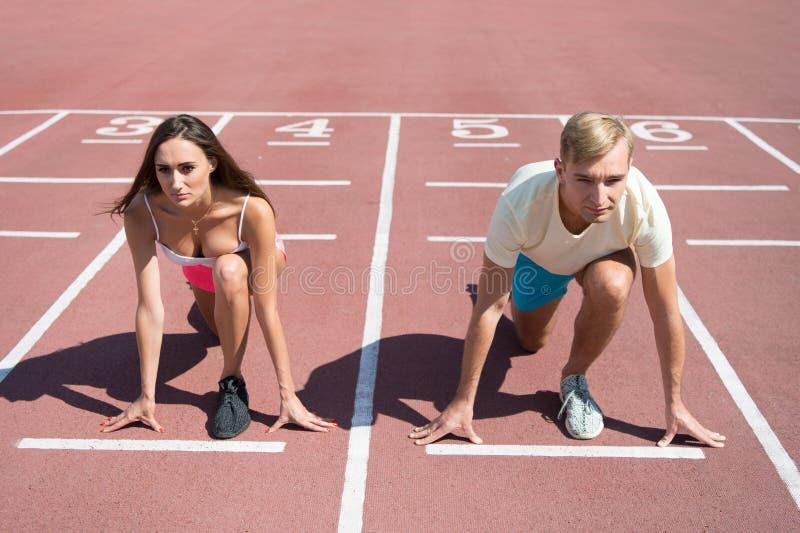 Gleichgestelltes zwingt Konzept Positionsrollbahnstadion des Mannes und der Frau niedriges Anfangs Laufender Wettbewerb oder Gesc lizenzfreie stockfotografie