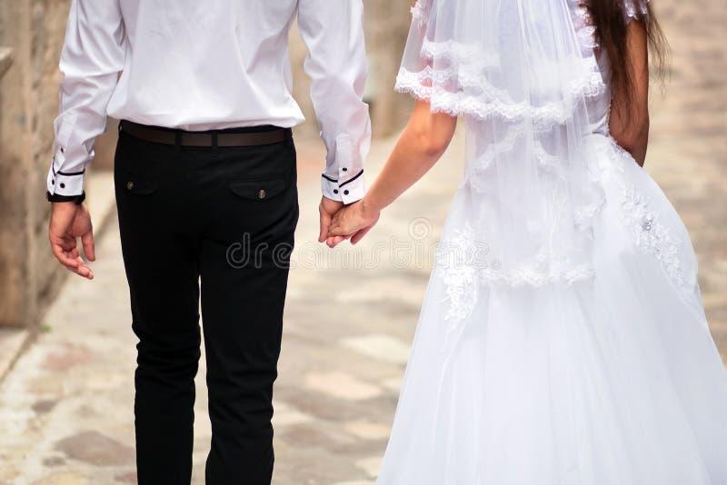 Gleichheit, Krawatte und Kristallschmucksachen Braut-und Bräutigam-Holding-Hände stockfotos