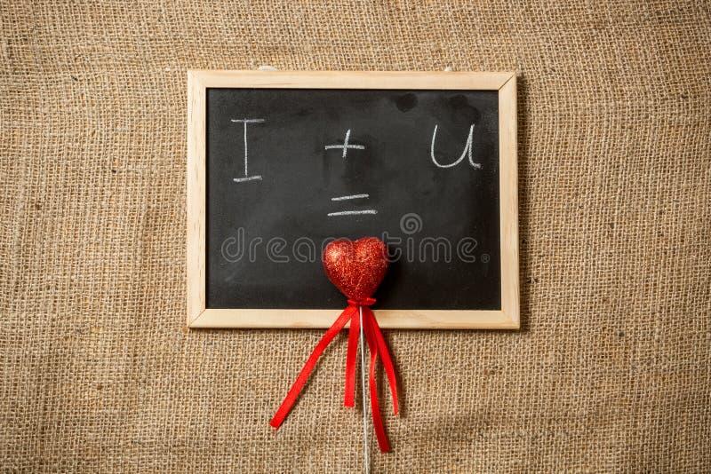 Gleichung der Liebe geschrieben auf Tafel mit rotem Herzen lizenzfreies stockfoto