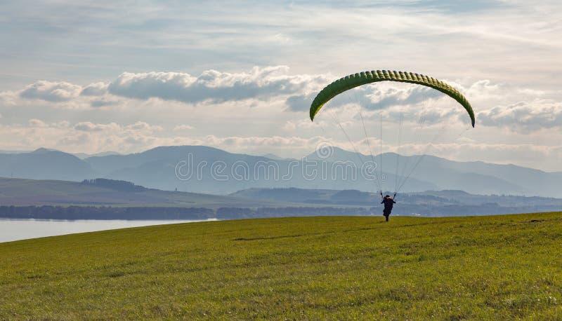 Gleitschirm beginnt Flug vom Hügel Extrem trägt Tätigkeit zur Schau lizenzfreie stockfotos